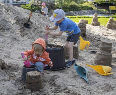 Lapset veistävät hiekkaa Itsenäisyydenpuiston hiekanveistoalueella.