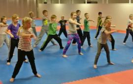 Lapset tatamilla harjoittelemassa taekwondo liikkeitä.